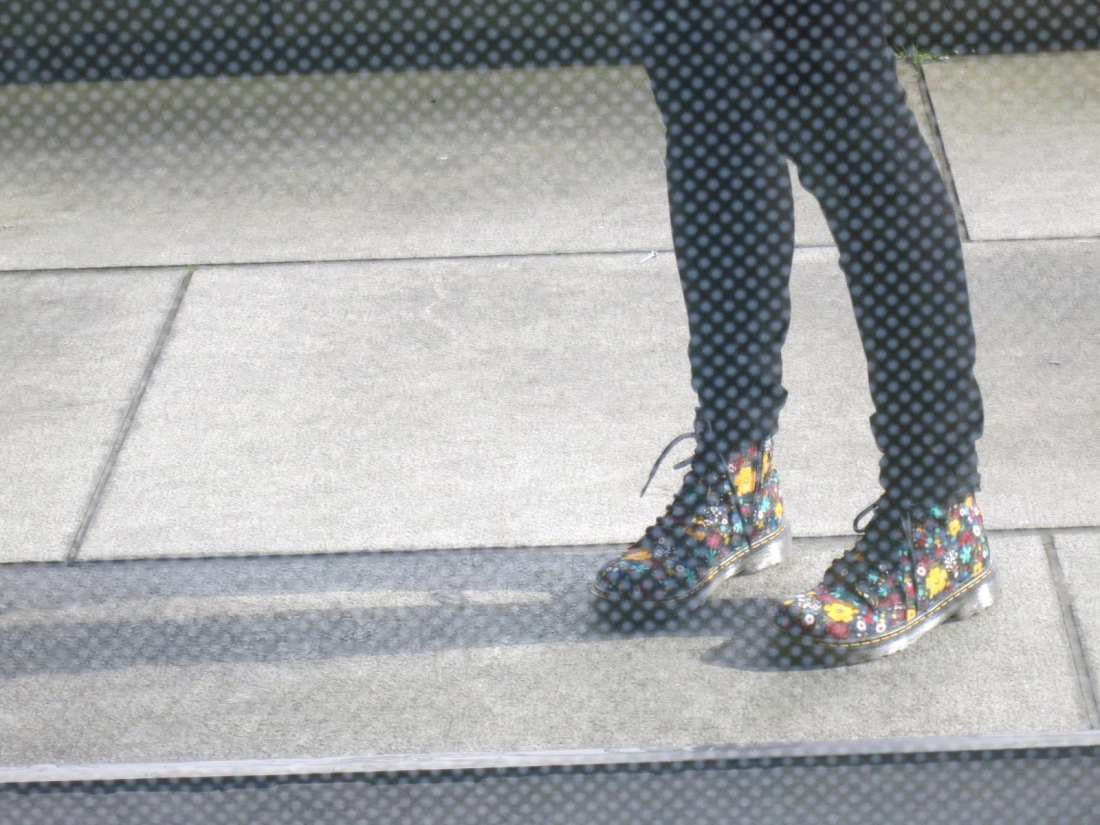 reflection of Dr Martens as seen in the Riverside Museum building window