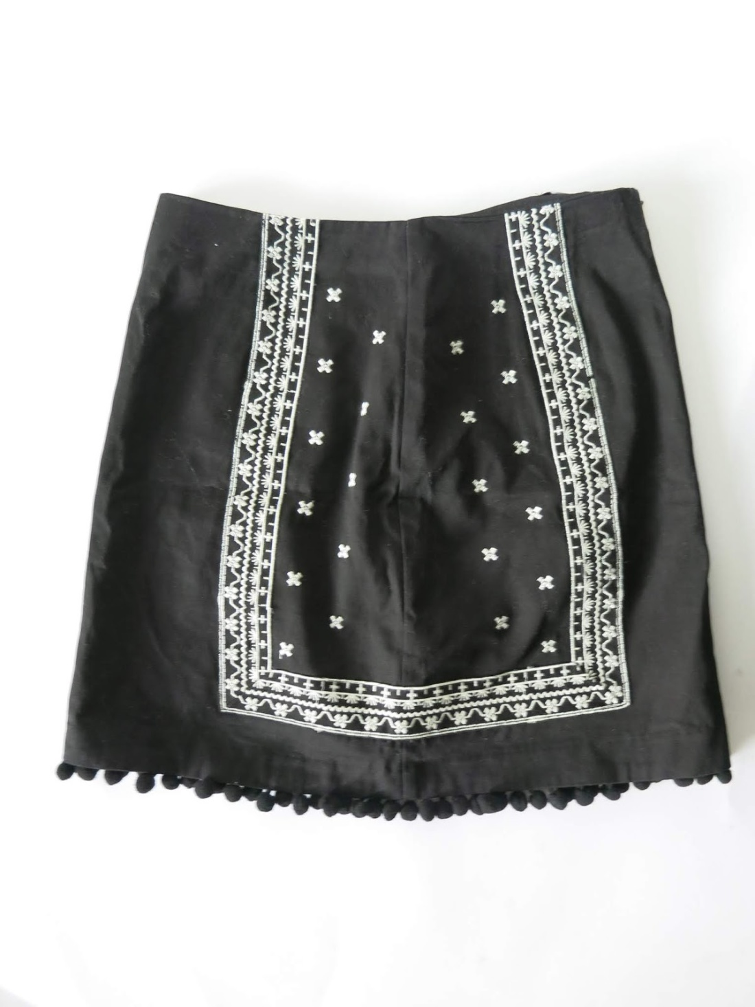 black skirt with pom-pom detailing and white embroidery
